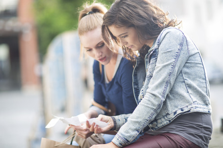 Two Female Friends Looking At Their Shopping Lists