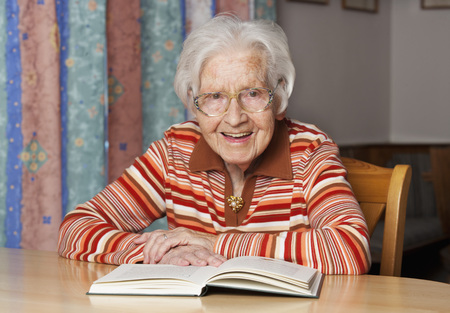 Portrait Of Smiling Senior Woman With Opened Book LANG_EVOIMAGES