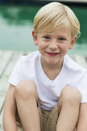 Portrait Of Smiling Little Boy Sitting On A Jetty LANG_EVOIMAGES