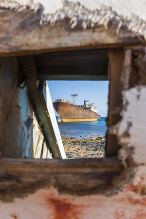 Spain, Canary Islands, Lanzarote, Arrecife, Punta Chica, Ship Wreck Telamon, Seen Through A Hole Of An Old Wooden Boat LANG_EVOIMAGES