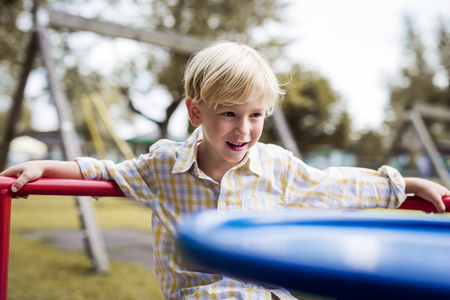Portrait Of Little Boy Watching Something On A Playground LANG_EVOIMAGES