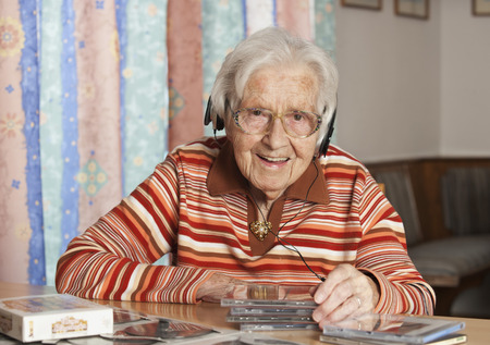 Portrait Of Smiling Senior Woman Hearing Cds With Headphones