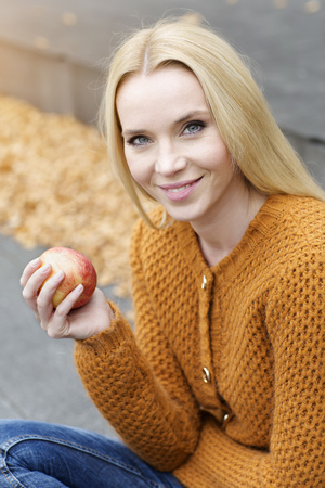 Portrait Of Smiling Young Woman Holding An Apple Wearing Cardigan