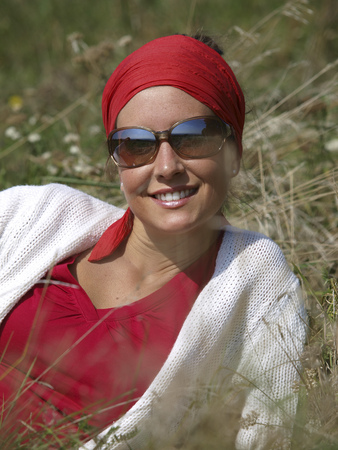 Portrait Of Smiling Young Woman Wearing Red Headscarf And Sunglasses