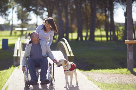 Woman With Man In Wheelchair And Dog In Park LANG_EVOIMAGES