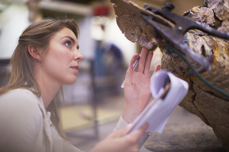 Young Woman In A SculptorS Workshop Checking Artwork
