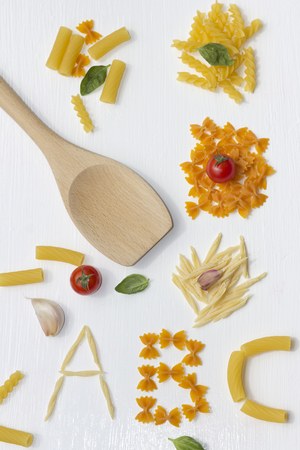 Different Noodles And Wooden Spoon On White Background
