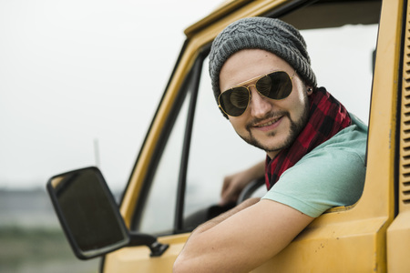 Smiling Young Man Sitting In Pick-Up Truck