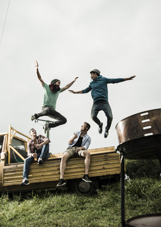 Two Friends Jumping From Pick-Up Truck