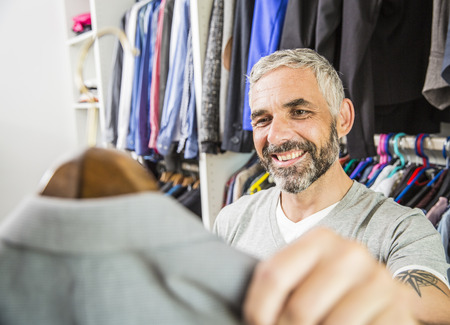 Portrait Of Smiling Man Choosing Jacket At His Walk-In Closet LANG_EVOIMAGES