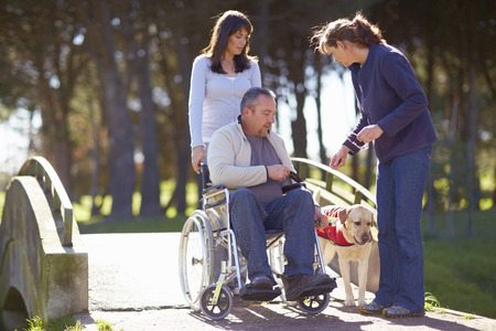 Man In Wheelchair With Two Women And Dog In Park