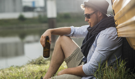 Young Man Leaning Against Vehicle Holding Bottle Of Beer