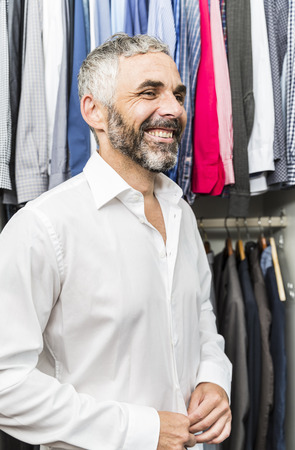 Portrait Of Smiling Businessman Buttoning His Shirt At His Walk-In Closet