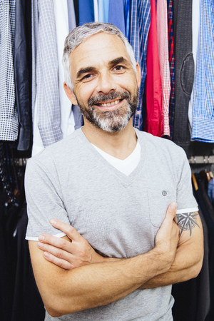 Portrait Of Smiling Man With Crossed Arms Standing At His Walk-In Closet