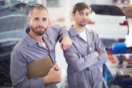 Two Car Mechanics With Clipboards In Repair Garage LANG_EVOIMAGES
