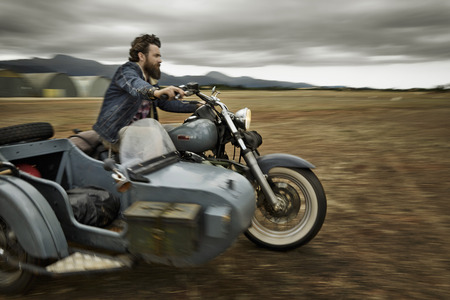 Man With Full Beard Driving Motorcycle With Sidecar LANG_EVOIMAGES
