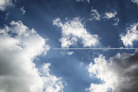 Vapour Trails Of A Plane In Sky With Clouds