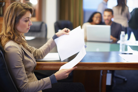Businesswoman Reading Document In Boardroom LANG_EVOIMAGES