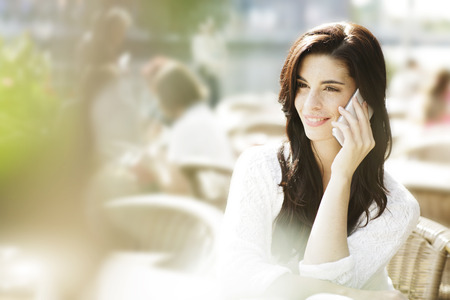 Smiling Young Woman Telephoning With Smartphone At A Pavement Cafe