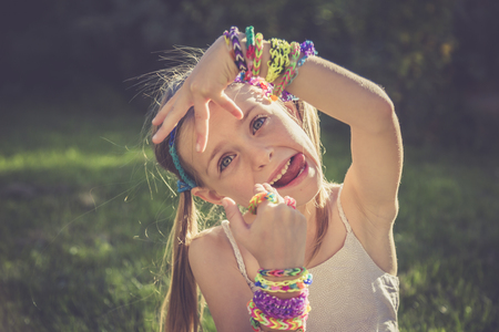 Portrait Of Little Girl With Outstretched Tongue Showing Her Loom Bracelets And Rings LANG_EVOIMAGES