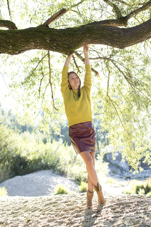 Young Woman Wearing Knit Pullover And Mini Skirt Relaxing In Nature