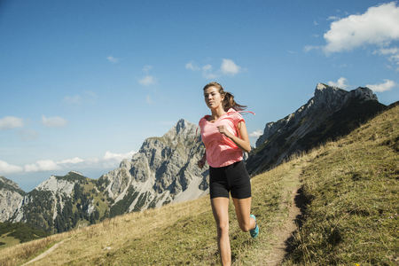 Austria, Tyrol, Tannheim Valley, Young Woman Jogging In Mountains