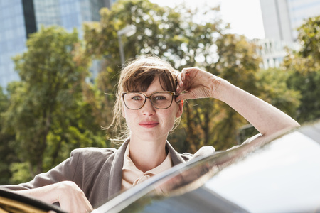 Portrait Of Businesswoman Leaning On Her Car