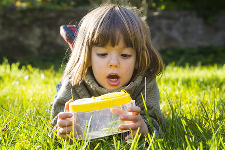 Little Girl Lying On A Meadow With Insect Can Watching Fire Bugs, Pyrrhocoridae