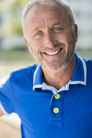 Portrait Of Smiling Mature Man Wearing Blue Shirt