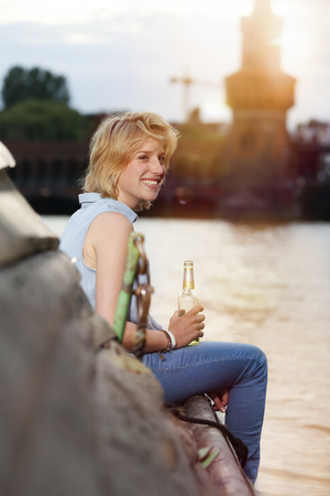 Germany, Berlin, Young Woman Enjoying Sunset At Spree River