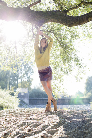 Portrait Of Young Woman Wearing Knit Pullover And Mini Skirt LANG_EVOIMAGES
