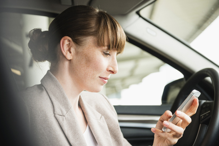 Portrait Of Businesswoman Sitting In A Car Looking At Her Smartphone