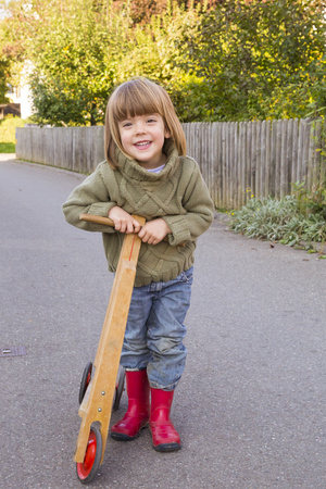 Smiling Little Girl With Wooden Scooter