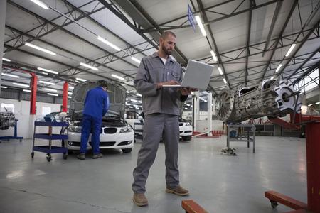 Two Car Mechanics With Laptop In Repair Garage
