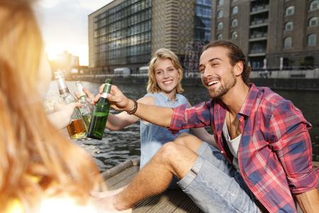 Germany, Berlin, Friend Sitting At Spree River, Drinking Beer