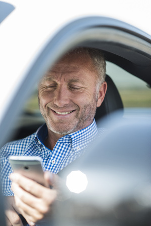 Businessman With Cell Phone In Car LANG_EVOIMAGES