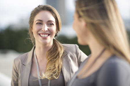 Portrait Of Smiling Businesswoman Communicating With Another One