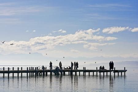 Germany, Bavaria, Upper Bavaria, Starnberg, Lake Starnberg, People On Jetty, Bavarian Alps And Zugspitze In The Background