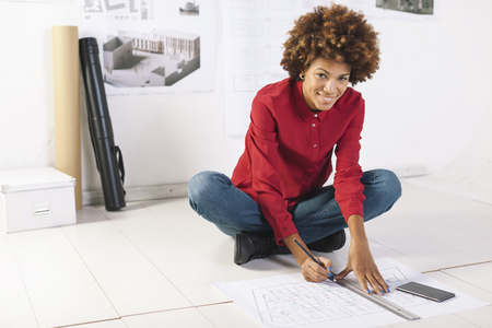 Young Female Architect Working On The Floor Of Her Office LANG_EVOIMAGES
