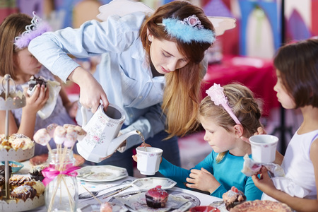 Girls And Teenage Girl On A Tea Party