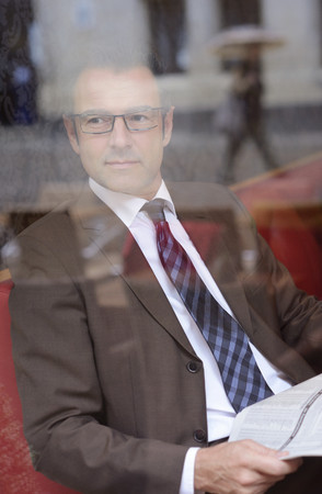 Businessman Sitting In A Cafe With Newspaper Watching Something