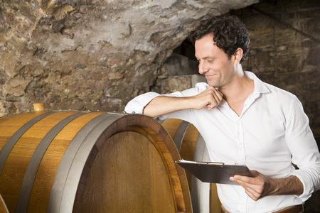 Man Holding Clipboard In Wine Cellar