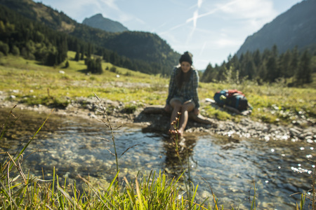 Austria, Tyrol, Tannheimer Tal, Young Female Hiker Relaxing At A Brook