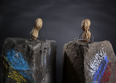 Peanut Manikins With Ukrainian And Russian National Colours Sitting On Opposite Stones LANG_EVOIMAGES