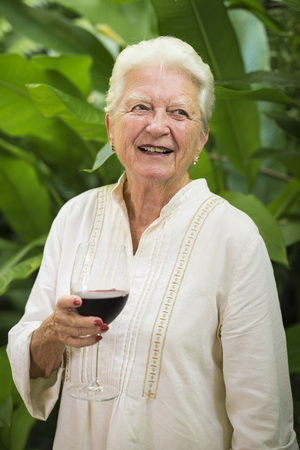 Portrait Of Smiling Senior Woman With Glass Of Red Wine LANG_EVOIMAGES