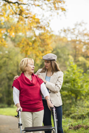 Senior Woman And Her Caring Adult Granddaughter Walking Together In Autumnal Park LANG_EVOIMAGES