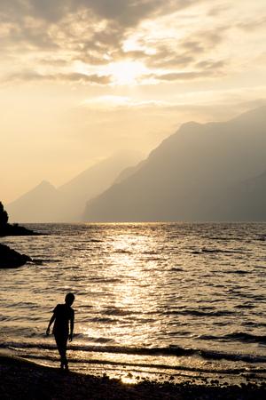 Italy, Veneto, Malcesine, Boy Standing At Lake Garda In Evening Light
