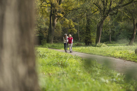 Senior Woman And Granddaughter Walking Together In A Park