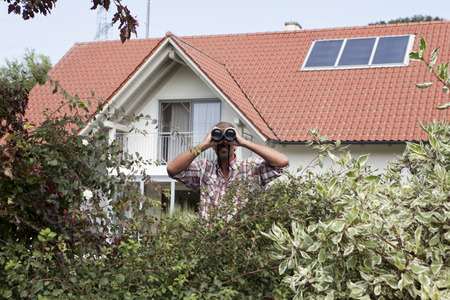 Man Looking Through Binoculars Over Hedge LANG_EVOIMAGES