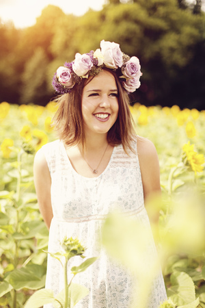 Portrait Of Smiling Young Woman Wearing Flowers Standing In Sunflower Field